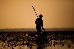 Pescador de la silueta en la puesta del sol. Fotos de archivo