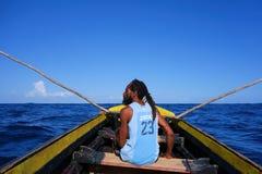 Pescador de Rasta en un barco de madera en el puerto Antonio, Jamaica Imagen de archivo
