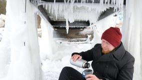 Pescador del hombre joven que se sienta con un termo en el lago y el té de consumición imagenes de archivo