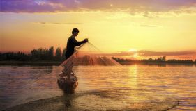 Pescador del lago en la acción al pescar Imagen de archivo