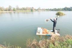 Pescador del lago en la acción al pescar Foto de archivo