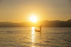Pescador del lago en la acción al pescar Imagenes de archivo