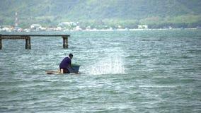 Pescador del lago en la acción al pescar en el crepúsculo, Tailandia almacen de video