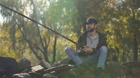 Pescador del trastorno que pesca en la orilla del río, actividad fastidiosa, mala suerte, agotamiento almacen de video