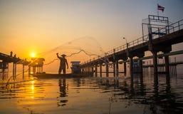 Pescador do lago Bangpra na ação ao pescar na manhã da luz do sol, Fotos de Stock