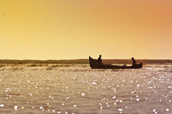 Pescador dos en el barco durante la salida del sol Imágenes de archivo libres de regalías