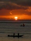 Pescador durante puesta del sol Imagenes de archivo