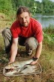 Pescador e um peixe fotos de stock