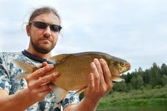 Pescador e um peixe imagem de stock