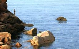 Pescador em cima das rochas da costa cor-de-rosa do granito em Bretagne Foto de Stock Royalty Free