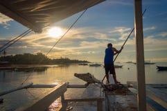 Pescador em um banka, barco de pesca filipino tradicional no por do sol, ilha de Cebu as Filipinas fotografia de stock
