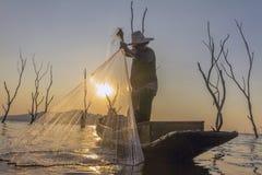Pescador em um barco de madeira com fundo do por do sol Foto de Stock