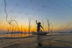 Pescador em um barco de madeira com fundo do por do sol Foto de Stock Royalty Free