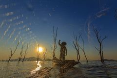 Pescador em um barco de madeira com fundo do por do sol Fotografia de Stock