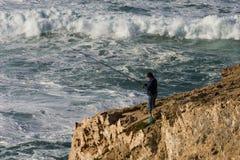 Pescador em um penhasco e em uma rocha fotos de stock