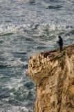 Pescador em um penhasco e em uma rocha Imagens de Stock