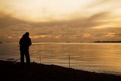 Pescador em uma costa de mar e por do sol majestoso sobre a água Imagem de Stock Royalty Free
