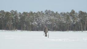 Pescador em uma pesca congelada do gelo do lago video estoque