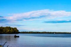 Pescador en barco en el lago con el velero en la distancia - el lago Erie fotografía de archivo libre de regalías