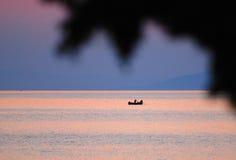 Pescador en barco en la puesta del sol Fotografía de archivo libre de regalías