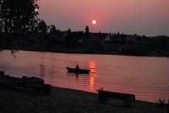Pescador en barco en la salida del sol imagenes de archivo