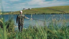 Pescador en capturas de la ropa del camuflaje almacen de metraje de vídeo