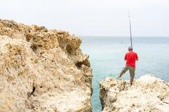 Pescador en costa Imágenes de archivo libres de regalías