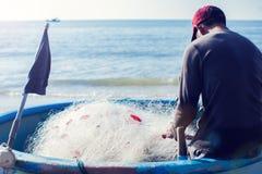Pescador en el barco con la red en manos imágenes de archivo libres de regalías