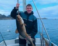 Pescador en el barco con los bacalaos Imagen de archivo libre de regalías