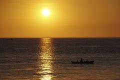 Pescador en el barco cuando puesta del sol Imágenes de archivo libres de regalías