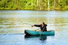 Pescador en el barco de goma foto de archivo libre de regalías