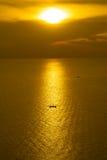 Pescador en el barco en el mar con puesta del sol Imagen de archivo libre de regalías