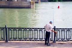 Pescador en el embarcadero con una caña de pescar Embarcadero con las verjas por el río Verjas del metal en el embarcadero Pescad fotos de archivo libres de regalías
