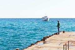 Pescador en el embarcadero en el Mar Negro Imagen de archivo libre de regalías