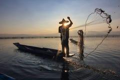 Pescador en el lago en la puesta del sol Imágenes de archivo libres de regalías