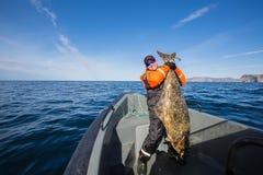 Pescador en el medio del mar con un pescado enorme Fotos de archivo