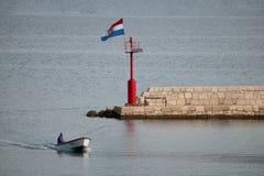 Pescador en el pequeño barco tradicional que entra en el puerto de Vinjerac, Croacia Foto de archivo libre de regalías