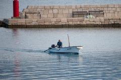 Pescador en el pequeño barco tradicional que entra en el puerto de Vinjerac, Croacia Fotos de archivo
