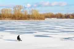 Pescador en el río congelado imagen de archivo