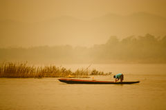 Pescador en el río en la puesta del sol Imagen de archivo