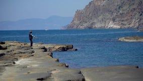 Pescador en formaciones de roca naturales en la playa de Koru, Gazipasa, Antalya, Turquía almacen de video
