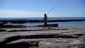 Pescador en formaciones de roca naturales en la playa de Koru, Gazipasa, Antalya, Turquía metrajes