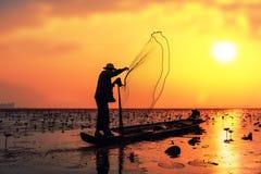 Pescador en la acción al pescar en el lago fotografía de archivo