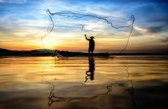 Pescador en la acción al pescar en el lago imagenes de archivo