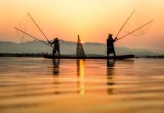 Pescador en la acción al pescar en el lago Imágenes de archivo libres de regalías