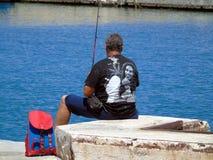 Pescador en la acción con la caña de pescar Imagen de archivo