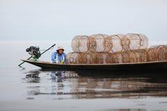 Pescador en la canoa con los desvíos de la pesca en el lago Inle Imagen de archivo libre de regalías