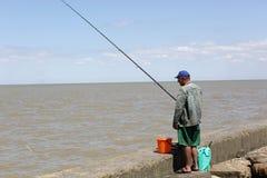 Pescador en la costa Foto de archivo