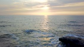 Pescador en la orilla rocosa de un mar tempestuoso en la salida del sol Encuesta aérea almacen de video