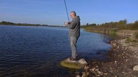 Pescador en la piedra cerca del lago que comprueba la caña de pescar almacen de video